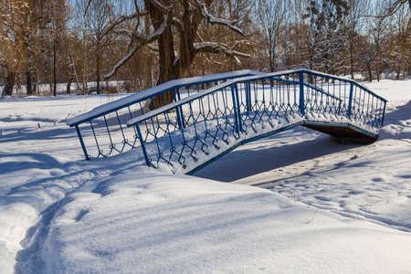 Landscape with snow-covered city park on a bright sunny winter day. Iron pedestrian bridge over a frozen river in the snow. Smila city, Ukraine Standard-Bild