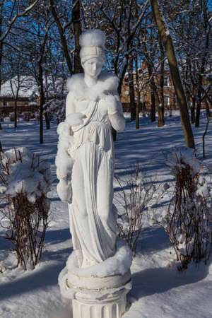 Snowy winter in the city park. Snow-covered statue of a woman on a background of snowy trees. Smila city, Ukraine