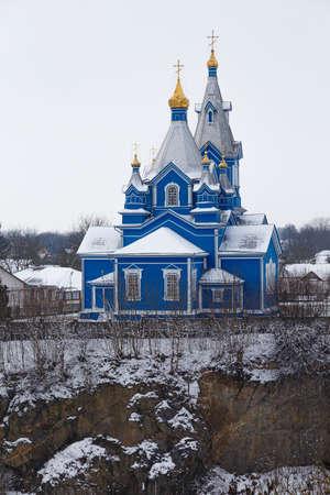 View on ancient ortodox church of Kosma and Demyan (Saints Cosmas and Damian) on rock, in the snow. Koretsk city. Rivne region. Ukraine.