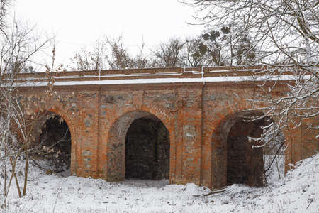 Arched stone bridge leading to the ruins of old abandoned Korets castle in the snow. Koretsk city. Rivne region. Ukraine. Tourist attraction.