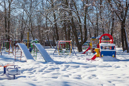 Empty playground in a city park, covered with snow. Location: Smila city, Ukraine