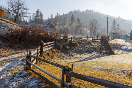 Sunny frosty foggy day in a mountain village, Yaremche. Winding road with a wooden fence. Carpathian mountains. Ukraine