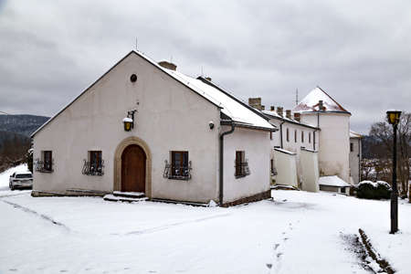 Ancient white castle in town Lesko (Kmita family castle) outside, at winter snowy day. Poland.