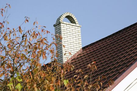 White brick chimney on the brown roof of the house Stockfoto