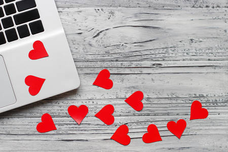 Background of a valentine on a wooden table with a laptop and hearts. Valentines Day greeting card. Top view