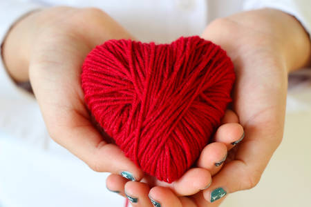 Childrens hands hold a heart of red thread for knitting. Valentines Day .