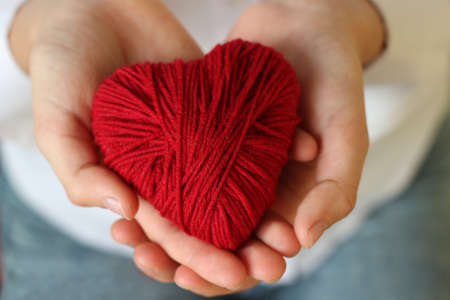 Children's hands hold a heart of red thread for knitting. Valentine's Day . Imagens