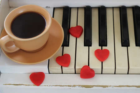 Red hearts and a cup of coffee are decorated with piano keys. Valentine's Day .
