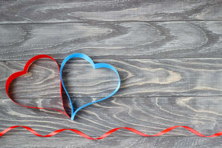 Valentine's Day . Two hearts of ribbons of red and blue on a background of wood. Imagens