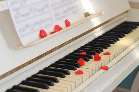Red hearts adorn piano keys. Valentine's Day . 写真素材