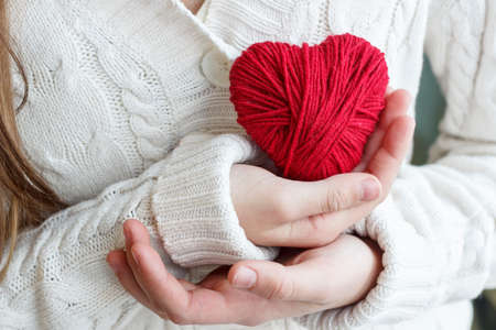 Childrens hands hold a heart of red thread for knitting.