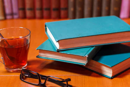 Stacks of colorful books on a wooden table, next to a cup of tea. the concept of reading habits. Banco de Imagens