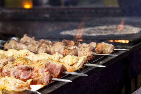 The process of cooking shish kebab on a metal grill in the open air.Grilling shashlik on barbecue grill. Marinated meat.