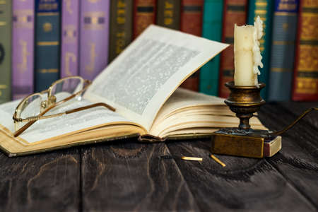 On the wooden background of the table there are stacks of colorful books near the old candlestick with burnt matches lying next to each other. Banco de Imagens