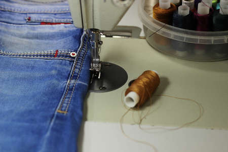 On the table of the sewing machine lie denim fabrics, close-up, next to the thread and scissors. Banco de Imagens