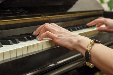 Hands of a girl playing on a white piano, close-up. 写真素材