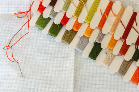 Set of multicolored threads for sewing and embroidering on a wooden background. Hobbies, clothes repair, atelier.