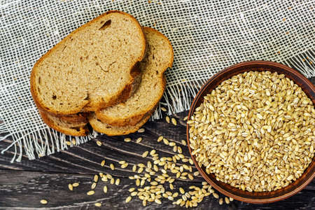 Slices of whole-wheat bread with wheat seeds on a wooden background