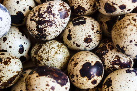 Quail eggs in a clay plate on a wooden background, a plate for storing quail eggs, a symbol of the Easter season. Healthy eating.