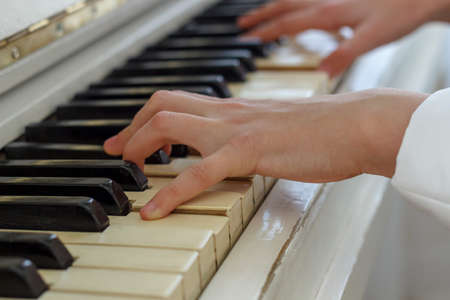 Hands of a young girl playing on a white piano, close-up.
