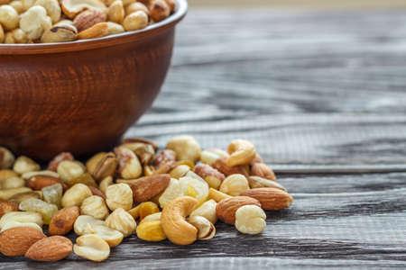 Mischen Sie Nüsse in Steingut auf einem hölzernen Hintergrund. Standard-Bild