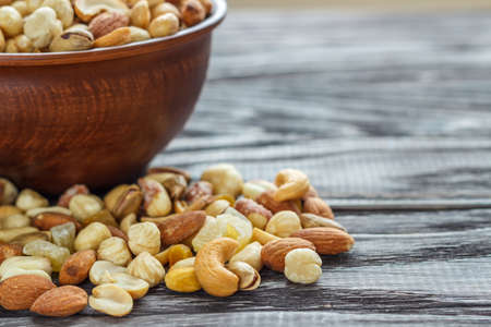 Mix nuts in earthenware on a wooden background. Archivio Fotografico