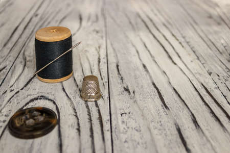 On a white wooden background is a spool of thread with a needle and a place for text.