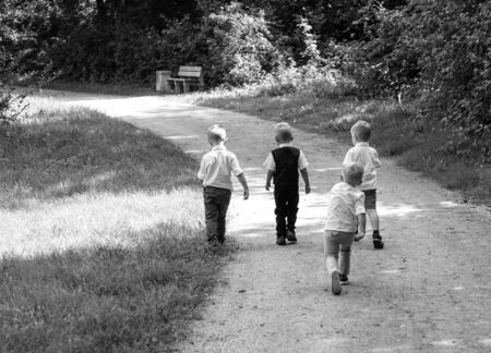 Group Of Children Running Along Path Towards In Park 스톡 콘텐츠