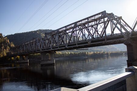 Railway bridge across the river in Russia. Travel through the mountains.