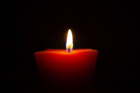Closeup of burning candle isolated on black background. Stock Photo