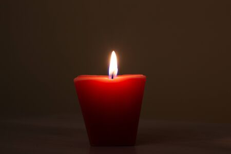 Closeup of burning candle isolated on black background.