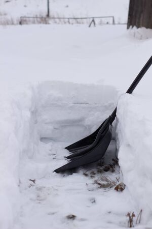City service cleaning snow winter with shovel after snowstorm yard. sunlight.