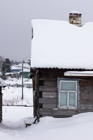 Wooden house in winter in the snow. A house with a chimney and a stove. Banque d'images - 135496432