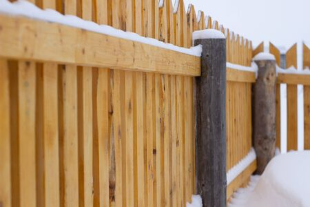 Winter landscape on the fence. Curved fence perspective view. Wooden village building. Banque d'images - 135496561