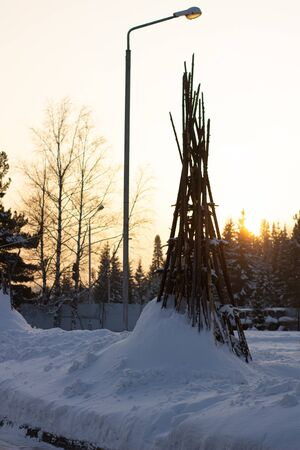 Tipi posts stuck in the thick snow in the middle of winter surrounded by lush green pines. Banque d'images - 135496562