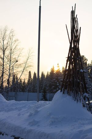 Tipi posts stuck in the thick snow in the middle of winter surrounded by lush green pines. Banque d'images - 135496700