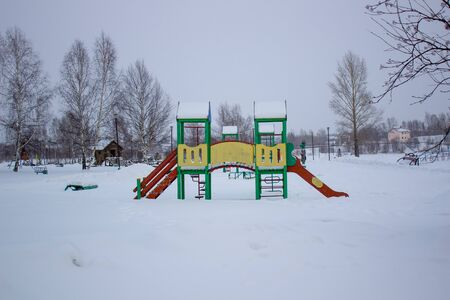 Paths in the winter Park. Bench, Playground for children