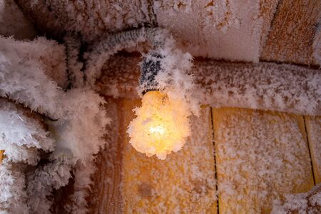 Snow crystals on a wooden wall and a light bulb Stockfoto