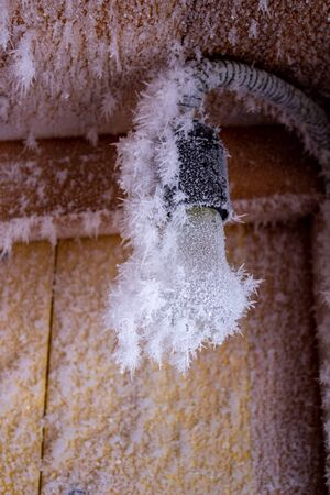 Snow crystals on a wooden wall and a light bulb.
