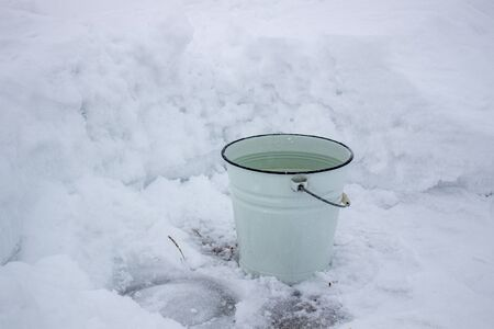 Bucket of water in the cold on the white snow