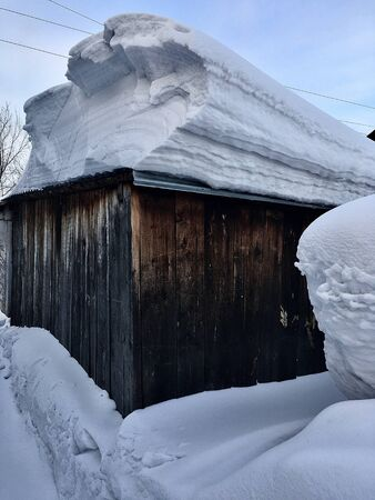 A lot of snow on the roof of the house and buildings. Winter in the country and in the city. Stockfoto