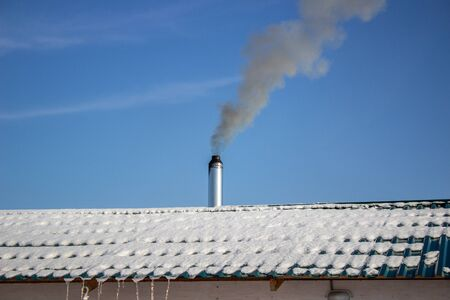 Modern steel chimney of a Russian sauna covered with snow against a blue sky 版權商用圖片