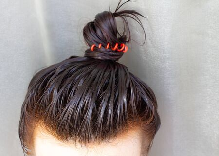 The girl puts the balm on her head. She gathered her hair into a bun.