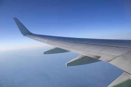 Airplane wing in the sky. View from a great height
