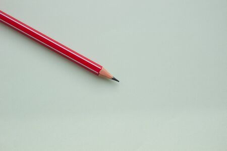 One red pencil on a light green background.