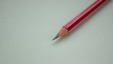 One red pencil on a light green background