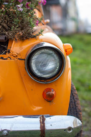 An old yellow car with round headlights and an open hood like a flower bed stands outside a flower shop in the city. Round headlight close-up Archivio Fotografico