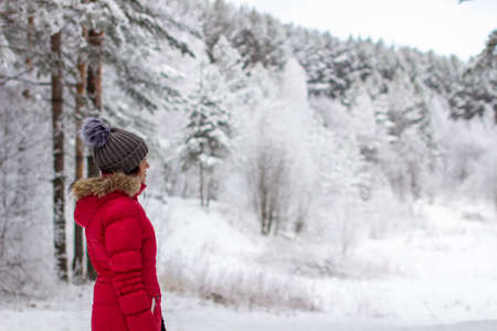 A young woman in a red jacket in a winter forest. Winter and frosty forest in the mountains. Nature walk