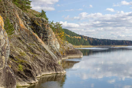 Beautiful, wide autumn river among forests and rocky shore.