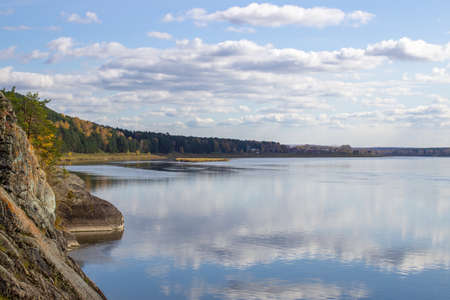 Beautiful, wide autumn river among forests and rocky shore. A calm and quiet place with autumn colors. Reflection of clouds in the water in good weather